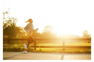 Healthy Woman Running On A Road