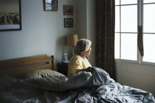 Senior Women in bed At Senior Living Home Care
