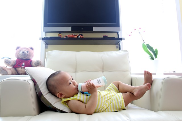 Adorable Asian Baby on Couch Drinking Baby Formula